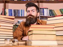 Man on strict face sit between piles of books, while studying in library, bookshelves on background. Teacher or student. With beard sit at table with glasses stock images