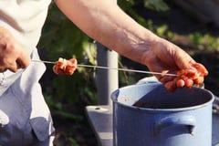 Man stringing meat on a skewer. Shashlik - cooking barbecue. Stringing meat on ramrod. Man stringing meat on a skewer. Shashlik - cooking barbecue. Stringing Royalty Free Stock Images