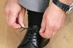 Man strings laces. A man strings laces on black shoes Royalty Free Stock Photography