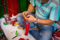 Man strings traditional beads during Hindu festival stock photography