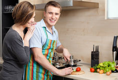 Man in striped apron slices vegetables for dinner Stock Photography