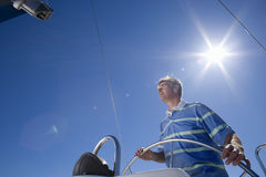 Man in striped blue polo shirt standing at helm of sailing boat out at sea, steering, low angle view (lens flare) Stock Image