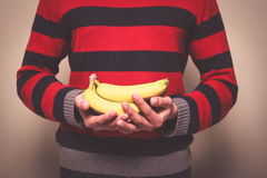 Man in striped jumper with bananas Royalty Free Stock Images