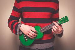 Man in striped jumper playing ukulele Royalty Free Stock Photo