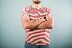 Man in striped shirt with arms crossed Stock Photo