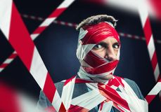 Man with stripped duct tape over body. Scared man with stripped duct tape over body royalty free stock photo