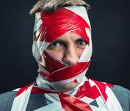 Man with stripped duct tape over body. Victum man with stripped duct tape over body royalty free stock photography