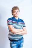 Man in stripped polo shirt on the gray background. Stock Photo