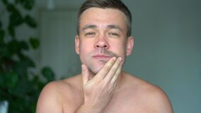 Man strokes first shaved cheek, and then stubble. skin care.