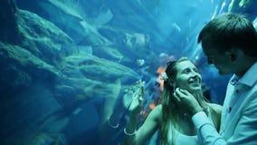 Man stroking the girl's face in underwater Aquarium Dubai Mall.  stock footage