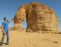 A man stroking the rock formation known as the Elephant Rock in Al Ula, Saudi Arabi KSA stock photo