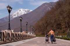 The man with the stroller on the embankment in the Roza Khutor in April. The man with the stroller on the embankment in the Roza Khutor Stock Photos