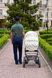 A man with a stroller walks in the park Royalty Free Stock Images