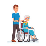 Man strolling with his grandmother in wheelchair Royalty Free Stock Photo