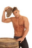 Man strong nos shirt barrel hat by head. A man with no shirt on putting his hat on his head royalty free stock photo