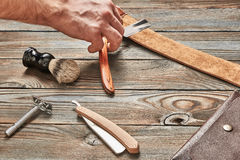 Man stropping straight razor with leather tool Royalty Free Stock Image