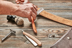 Man stropping straight razor with leather tool Royalty Free Stock Photos