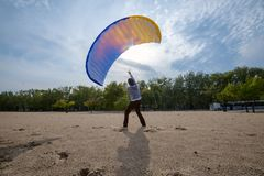 Man struggles with the wind, while training with a paraglider Stock Photos