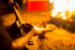 Man strumming an ukulele/guitar in the woods next to an open bonfire. A person relaxing while sitting next to a campfire on a beach, playing a guitar royalty free stock photography