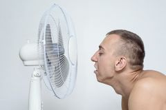 Man with stubble on his face suffers from the heat and trying to cool off near the fan royalty free stock images