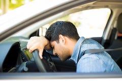 Man stuck in traffic jam. Young hispanic man sleeping on steering wheel of car during a traffic jam royalty free stock photography