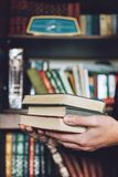 Man, Student holding many books in hands on the background of bookshelves. Male hands hold a large stack of books. Read reading online free classic club time stock images