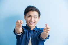 Man student pointing to you. Man student smile and pointing to you isolated on blue background,asian Royalty Free Stock Images