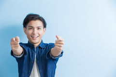 Man student pointing to you. Man student smile and pointing to you isolated on blue background,asian Royalty Free Stock Photography