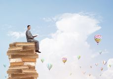 Man student reading book and aerostats flying around in air. Young businessman sitting on pile of books with one in hands Stock Photos