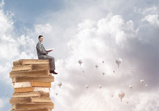 Man student reading book and aerostats flying around in air. Young businessman sitting on pile of books with one in hands Royalty Free Stock Image