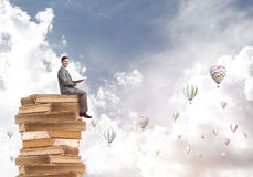 Man student reading book and aerostats flying around in air Stock Image