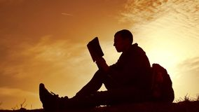 Man student reading in the park with backpack against sunset. Silhouette of man reading book at sky sunset lifestyle. Man student reading in park with backpack stock video footage