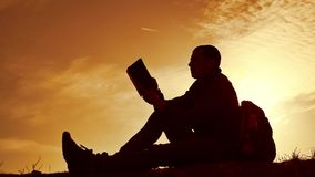 Man student reading in the park with backpack against sunset. Silhouette of man reading book at sky sunset nature. Man student reading in park with backpack stock footage