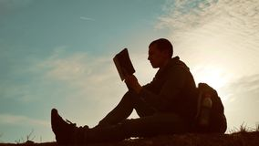 Man student reading in the park with backpack against sunset. Silhouette of man reading book lifestyle at sky sunset. Man student reading in park with backpack stock footage