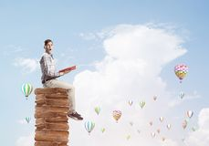 Man student on stack reading book and aerostats flying around stock photography