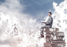 Man student on stack reading book and symbols flying around. Young businessman sitting on pile of books with one in hands Royalty Free Stock Photography