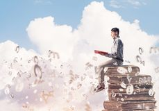 Man student on stack reading book and symbols flying around. Young shocked man in casual sitting on pile of books with one in hands Stock Photography