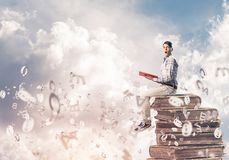 Man student on stack reading book and symbols flying around. Young shocked man in casual sitting on pile of books with one in hands Royalty Free Stock Photo