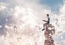Man student on stack reading book and symbols flying around. Young shocked man in casual sitting on pile of books with one in hands Stock Image