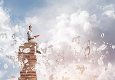Man student on stack reading book and symbols flying around. Young shocked man in casual sitting on pile of books with one in hands Royalty Free Stock Image