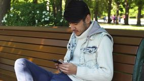 Man student surfing in internet using smartphone. Sitting in the park stock video footage