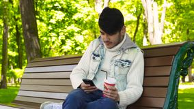 Man student surfing via smartphone. Man student surfing internet via smartphone sitting on bench in the park stock footage