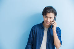 Man student talk on phone. Isolated on blue background,asian Stock Images
