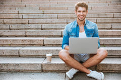 Man student using laptop while sitting on the staircase outdoors. Young casual smiling man student using laptop while sitting on the staircase outdoors with cup stock image