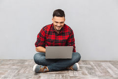 Man student working on laptop while sitting on the floor. Portrait of a friendly happy man student working on laptop while sitting on the floor isolated over Royalty Free Stock Photo