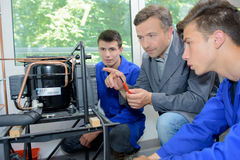 Man and students looking at invention. Man and students looking at an invention stock photography