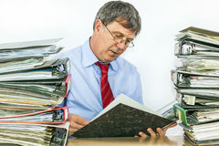Man studies folder with files at. Man studies many folder with files at his desk in the office stock images