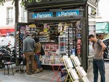 Man studies magazine headline at Place des Vosges newsstand, Par Stock Photos