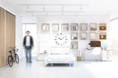 Man in a studio apartment with bed, clock and bike Royalty Free Stock Images