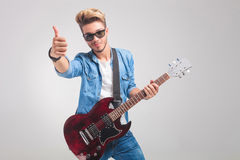 Man in studio holding a guitar while showing the victory sign. Portrait of young man in studio holding a guitar while showing the victory sign looking at the Stock Photography